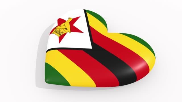 stockvideo's en b-roll-footage met heart in kleuren en symbolen van zimbabwe op witte achtergrond, lus - ridderlijkheid