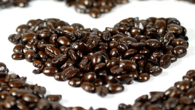 Heart of coffee beans on the table, top view video