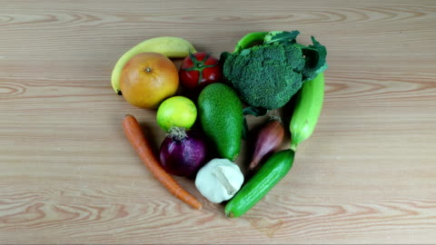 cuore su legno frutta stop motion - alimentazione sana video stock e b–roll