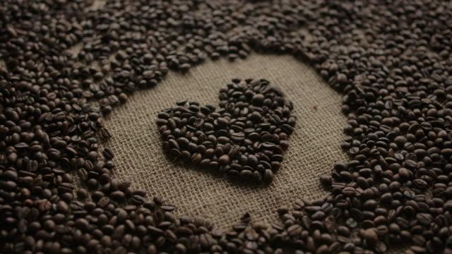 vídeos de stock e filmes b-roll de heart pictogram laid out with dark coffee beans by neat hands with care and love - coração fraco