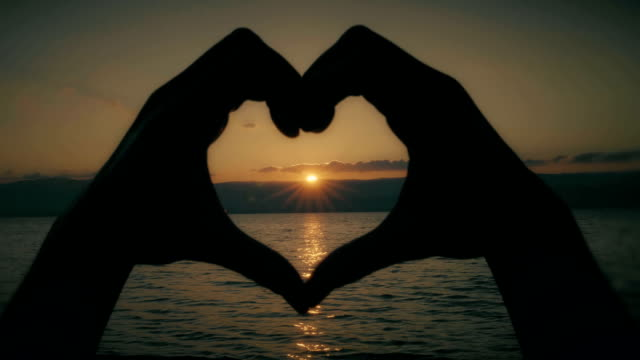 Heart shape hands. Sunset over water. Female hands make the share of a heart, the sun is setting and reflecting on the water. falling in love stock videos & royalty-free footage