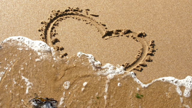 Heart shape in sand, washed away by tide. A heart shape is drawn in the sand on a beach. Waves roll in and wash the drawing away. falling in love stock videos & royalty-free footage