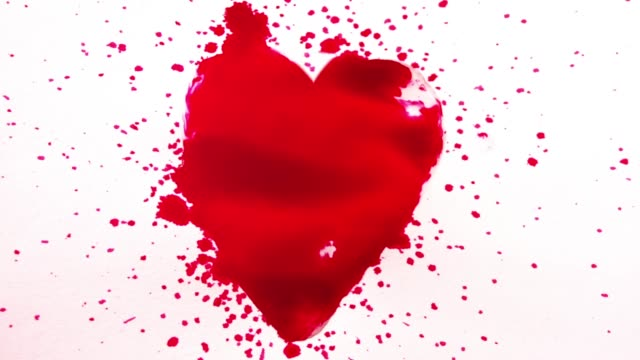 Heart shape made from falling splashes of red ink video