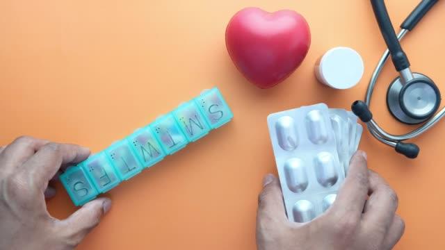 stockvideo's en b-roll-footage met het symbool van de hartvorm, stethoscoop, pillendoos en blaarpak op oranje achtergrond - doordrukstrip