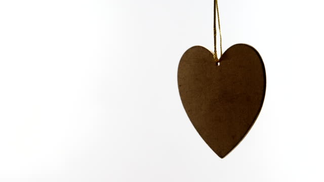 heart shaped decoration hanging in mid air 4k - simbolo concettuale video stock e b–roll