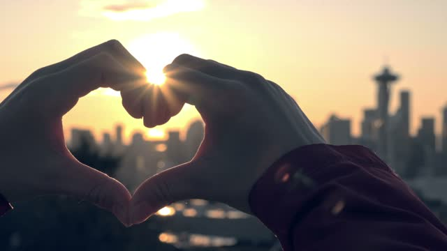 Heart shaped hand gesture with bright sun and Seattle behind video