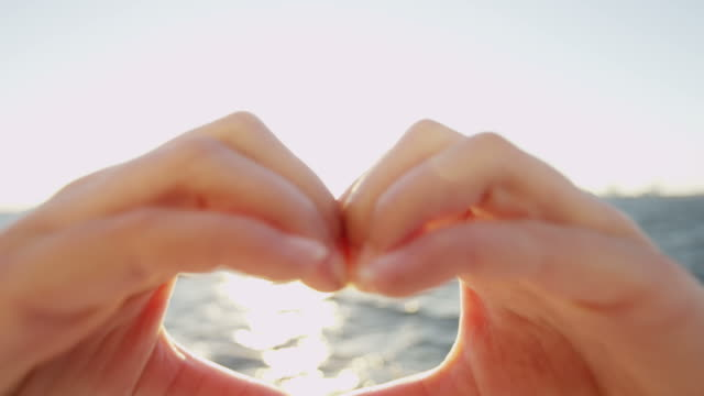 Heart shaped hands showing ocean social networking greeting