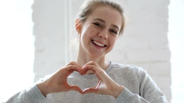 heart sign by young woman in love, hands gesture - gestykulować filmów i materiałów b-roll