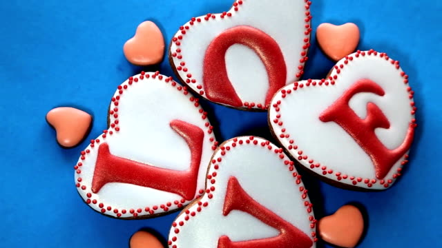 Heart-shaped gingerbread cookies on a blue rotatin surface. video