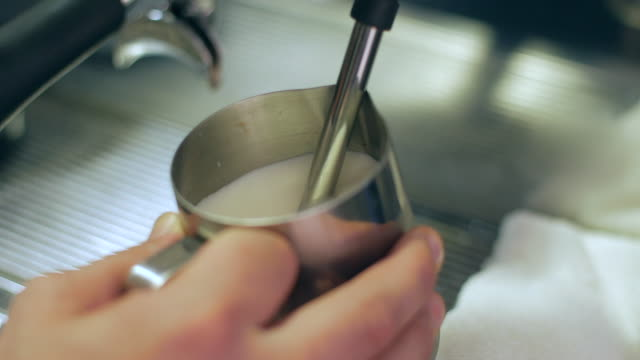 heating milk in a professional coffee machine in order to make a latte or cappuccino - pentola a vapore video stock e b–roll