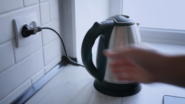 heating of kettle with water close-up on white wooden table in room. close up. - teapot stock videos & royalty-free footage