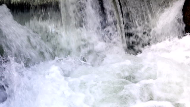 heaving frothy waterfall created by water pressure on the dam of the river video