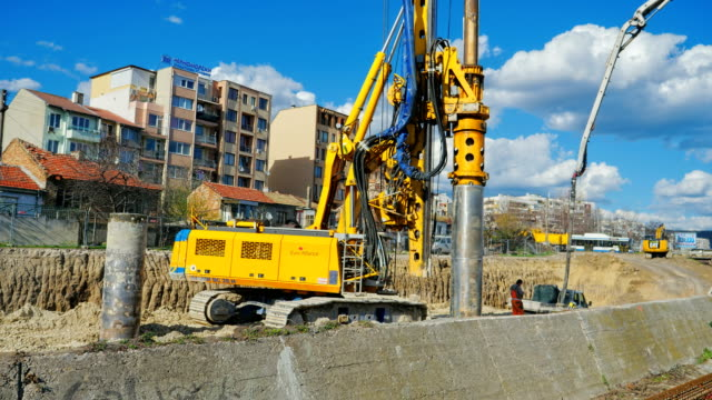 Heavy big excavator break trough holes for concrete colones for new road in construction site. Building a new streets in urban area, city town construction vehicle stock videos & royalty-free footage