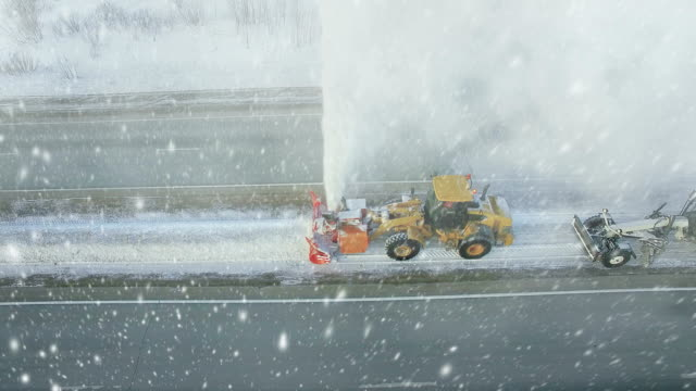 vídeos de stock e filmes b-roll de heavy big storm snow fall, grader clean remove snow, snowplow, snow blower, blast snowfall, winter, road, special vehicle on the highway, cool frozen fountain of snow aerial view - remover