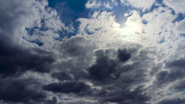 Heavy dark rain storm clouds and sun light shafts shining through blue sky, sunset timelapse
