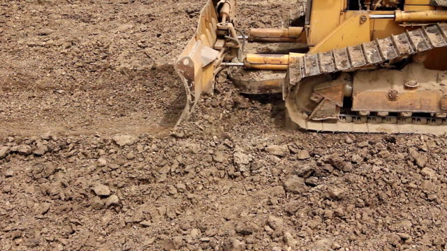 Heavy earthmover, bulldozer machine is leveling construction site video