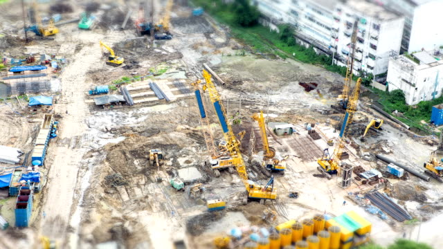 heavy equipment and workers walk at a construction site. (timelapse) - concrete architecture stock videos & royalty-free footage