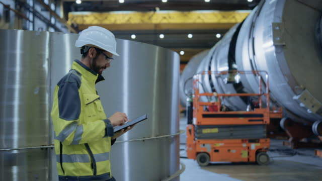 Video Heavy Industry Engineer Walk Through Pipe Manufacturing Factory, Use Digital Tablet Computer. Facility for Construction of Oil, Gas and Fuel Pipeline Transportation Products. Side View Slow Motion
