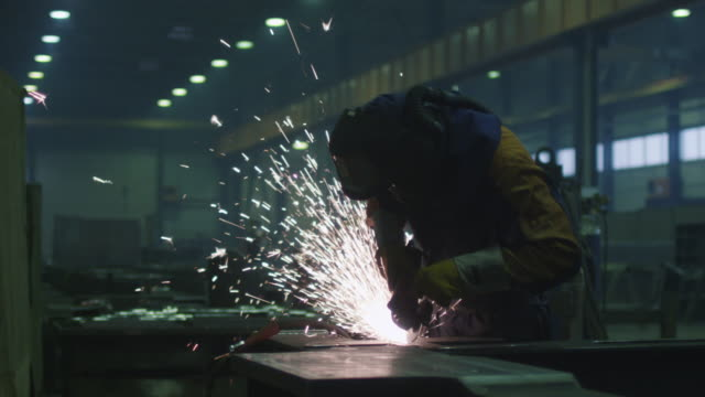 vídeos de stock e filmes b-roll de heavy industry worker at a factory is working with metal on a angle grinder while hot sparks are produced in a result. - moedor