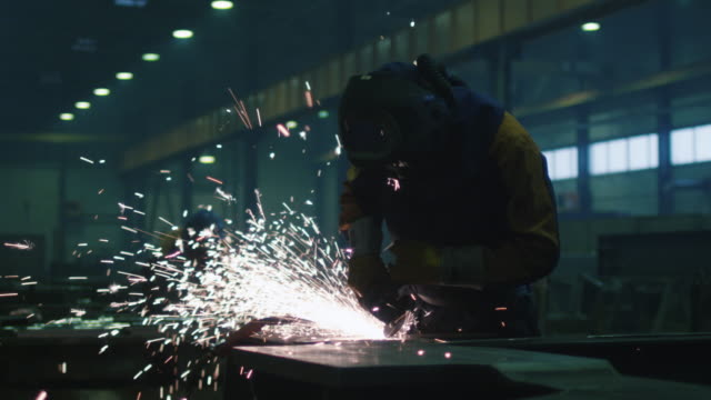 Heavy industry worker at a factory is working with metal on a angle grinder while hot sparks are produced in a result. Heavy industry worker at a factory is working with metal on a angle grinder while hot sparks are produced in a result. metallurgy stock videos & royalty-free footage