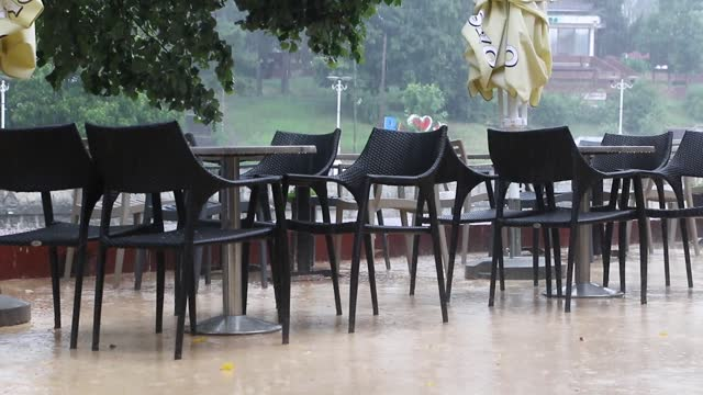 Heavy rain at empty outdoor coffee shop.