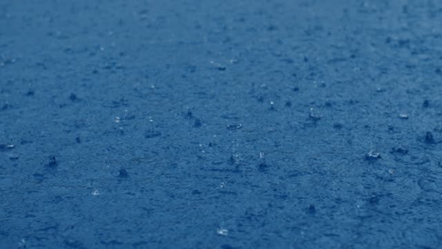 Heavy rain on blue water surface in slow motion Heavy rain on water surface. Raindrops beat on the surface of the water. 180 fps drenched stock videos & royalty-free footage
