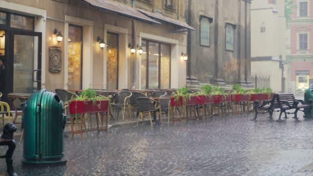 カフェのテーブルと椅子の外に落ちる重い雨滴 - テーブル 無人のビデオ点の映像素材/bロール