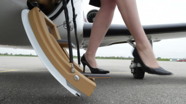 Heels and Jet Executive woman's legs with high heels exiting and then boarding a private jet.  Close up from front angle. private airplane stock videos & royalty-free footage