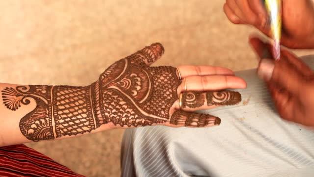 Heena mehndi artist making a design on woman hand video