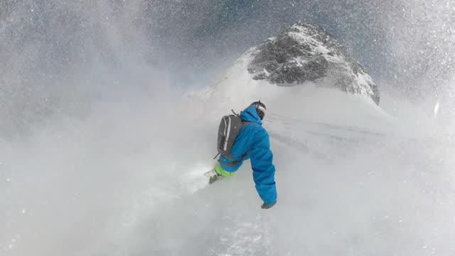 vídeos de stock e filmes b-roll de follow: heliboarder shredding untouched mountain terrain on sunny winter day. - desporto radical