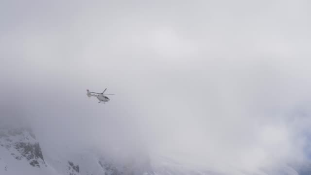vídeos de stock e filmes b-roll de a helicopter flies through the high mountains - resgate