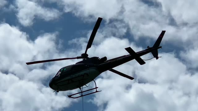 Helicopter Flying Against Blue Sky and Clouds