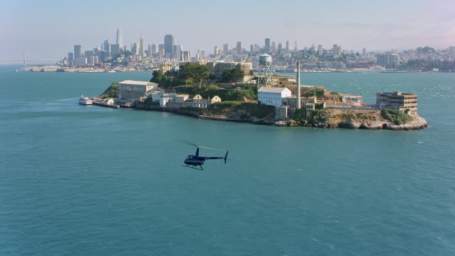 AERIAL Helicopter flying along the Alcatraz Island with San Francisco in the background