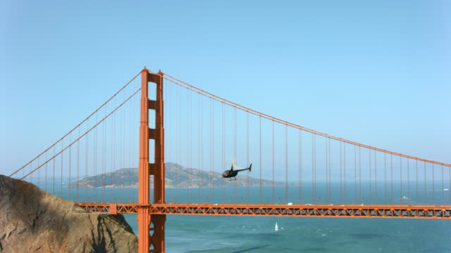 AERIAL helicopter flying along the Golden Gate Bridge in San Francisco, CA in sunshine