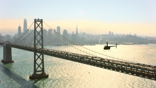AERIAL Helicopter flying along the San Francisco-Oakland Bay Bridge in San Francisco, CA