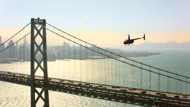 AERIAL Helicopter flying along the San Francisco-Oakland Bay Bridge overlooking the San Francisco Downtown in the background