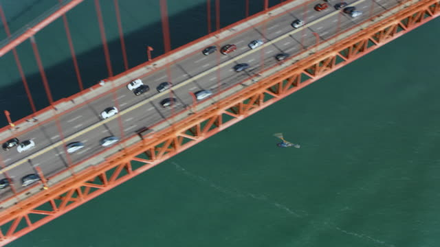 AERIAL helicopter flying below the Golden Gate Bridge in San Francisco, CA in sunshine