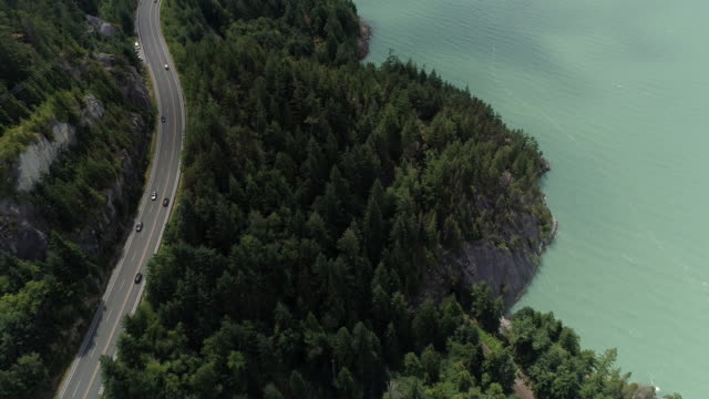Helicopter Flying Over Cars on Coastal Mountain Highway by Ocean Cliffs Transportation aerial of travelers on road trip up Sea to Sky highway along How Sound in British Columbia vancouver canada stock videos & royalty-free footage