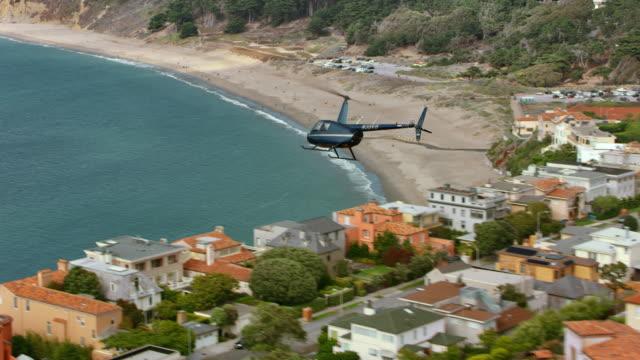 晴れた日に海に向かって、サンフランシスコの街の上を飛んで空中のヘリコプター - ヘリコプター点の映像素材/bロール