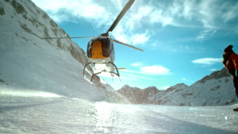 SLO MO LD Helicopter hovering above the icy ground Slow motion locked down low angle shot of a helicopter hovering above the icy ground on the top of the mountain in winter. helicopter stock videos & royalty-free footage