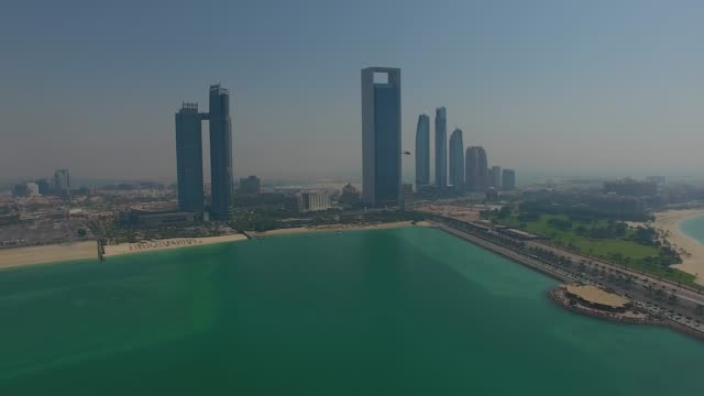 helicopter in front of abu dhabi urban skyline - abu dhabi стоковые видео и кадры b-roll