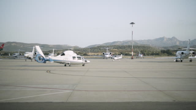 A helicopter is preparing to take off while a scheduled airliner lands video