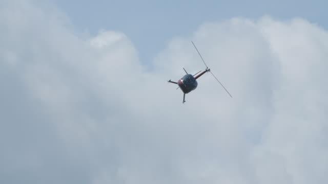 hubschrauber macht schleife und manövrieren diagonal und fliegen durch den himmel - gefreiter stock-videos und b-roll-filmmaterial