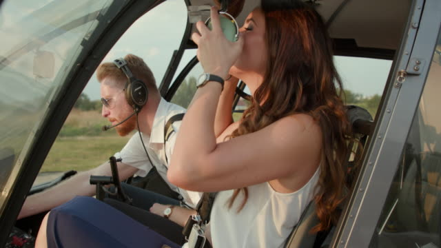 Helicopter pilot and female passenger closing doors before take off