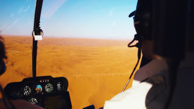CU Helicopter pilot and passenger flying over Deadvlei sand dunes,Namibia,Africa Helicopter pilot and passenger flying over Deadvlei sand dunes,Namibia,Africa. Real Time. Shot in 8K resolution. extreme terrain stock videos & royalty-free footage