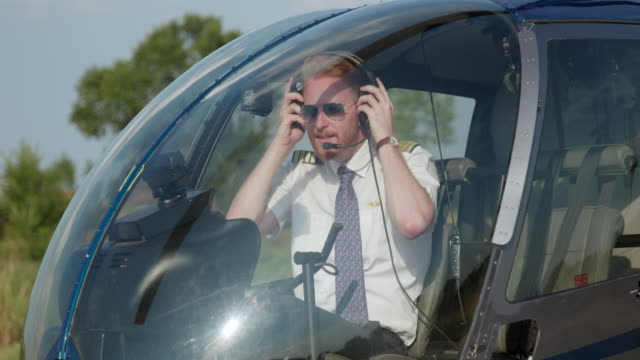 Helicopter pilot checking headphones and steering wheel in cockpit