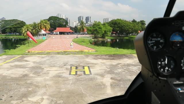 Helicóptero, preparándose para aterrizar en un helipuerto cerca de un lago - vídeo