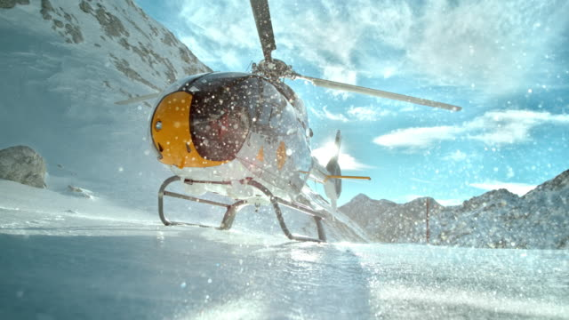 SLO MO Helicopter rotors make ice particles shine in sun Slow motion locked down low angle shot of a yellow helicopter on an icy surface on the top of the mountain and its rotors are making icy particles to fly around and shine in the sun. propeller stock videos & royalty-free footage