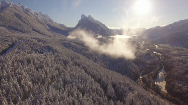 Helicopter Shot Flying Through Cloud Over Snowy Mountain Valley with Blue Sky video