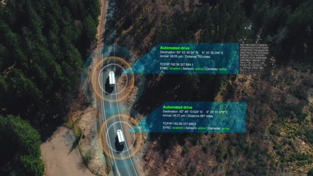 詳細を示し、技術アシスタントの追跡情報と森林ハイウェイを駆動するセルフドライビングトラックのヘリコプターのショット。視覚効果クリップ - トラック点の映像素材/bロール